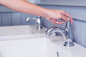 hand-turning-faucet-on-sink